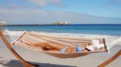 Beautiful woman relaxing in hammock on beach Stock Footage