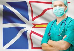 Surgeon with Canadian privinces flag on background - Newfoundland and Labrado - stock photo