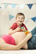 Cute small boy playing on the mother's belly Stock Photos