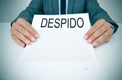 Businessman shows a document with the text despido, dissmissal in spanish Stock Photos