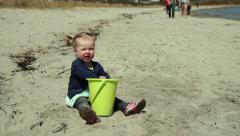 Little girl putting sand in a bucket on the beach, people walking, medium shot Stock Footage