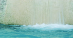Clean blue water stream with splashes falling from small waterfall, loop video - stock footage