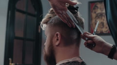 Woman barber cutting hear of client with scissors and comb, close up - stock footage