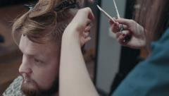 Woman barber cutting hear of client with scissors and comb, close up Stock Footage