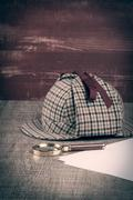 Sherlock Hat and magnifying glass - stock photo