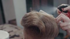 Woman barber makes styling hair with spray and comb, slow motion, close up Stock Footage