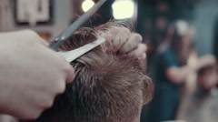 Barber woman cutting hear of client with scissors and comb, close up - stock footage