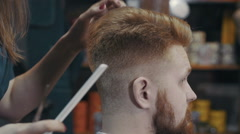 Barber woman cutting hear of client with scissors and comb at barbershop - stock footage