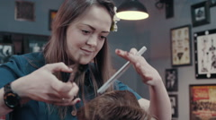 Barber woman cutting hear of client with scissors and comb at barbershop Stock Footage