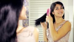 Cute girl brushing long black hair in front of mirror at home closeup - stock footage