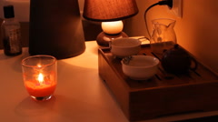 Candle burns, tea board, kettle on the table Stock Footage