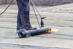 Propane blowtorch at floor slab insulation work - stock photo