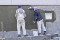 Workers plastering a outdoor wall 3 - stock photo