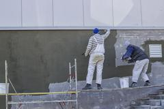 Workers plastering a outdoor wall - stock photo