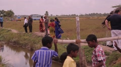 Indian adults and kids walking alongside the ditch - stock footage