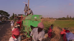 Group of n people working with hay and grains in India - stock footage