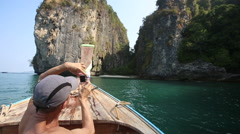 Old man photos bay from longtail boat drifting to island Stock Footage