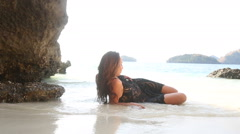 Brunette girl in lace frock lies sagging half in water Stock Footage