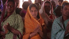 Indian women in an orange sari singing and clapping at church Stock Footage