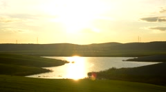 Lake landscape in green field, with sun reflection in the water Stock Footage
