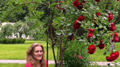 Big rose flower bush and pregnant woman throw rose petals - stock footage