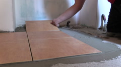 Hand put ceramic tile on cement glue at home floor Stock Footage