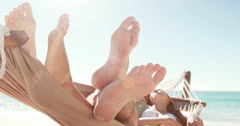 Couple relaxing in hammock at the beach - stock footage