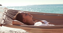 Woman relaxing in hammock at the beach - stock footage