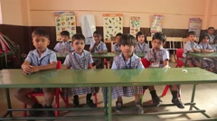 Indian kids sitting at the desks and waving - stock footage