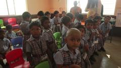 Indian children receiving candies at school - stock footage
