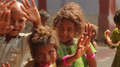 Little Indian girl in a green dress and other kids waving and smiling - stock footage