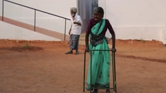 Old woman walking with a zimmer frame in India Stock Footage