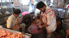 Indian man cleaning chopping table at a butchery in Mumbai. - stock footage