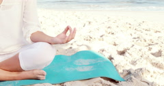 Woman sitting on the beach in lotus pose Stock Footage