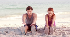 Smiling couple stretching their legs on the beach Stock Footage