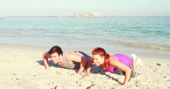 Smiling couple doing push ups at the beach Stock Footage