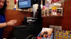 Attractive female worker at checkout counter inside petsmart store. Stock Footage