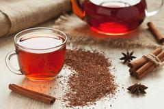 Healthy african rooibos tea in glass cup with spices on vintage table Stock Photos