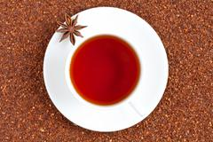 Red traditional rooibos tea full of antioxidant in white cup with star anise Stock Photos