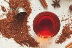 Cup of tasty organic herbal rooibos red tea with spices on vintage table Stock Photos