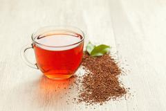 Glass cup of healthy natural herbal rooibos tea on wooden table Stock Photos