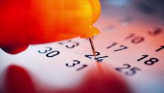 Human hand placing a push pin on calendar - stock footage
