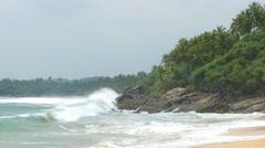 Large ocean waves breaking on the rocks of tropical coast 4k Stock Footage