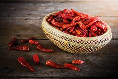 Dried Chili Peppers in Bamboo Basket on wooden table - stock photo