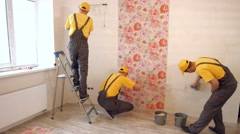 Builders hang wallpaper in the apartment. - stock footage