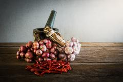 Dry chili pepper and red onion and garlic and stone mortar on an old wooden b Stock Photos