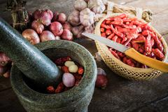 dry chili pepper and red onion and garlic and stone mortar on an old wooden b - stock photo