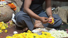 Man making garland of flowers on the market in Goa, India Stock Footage