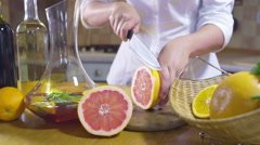 Woman cutting slices of grapefruit slow motion Stock Footage