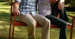 Couple relaxing in the park on bench - stock footage
